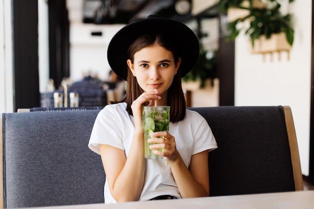 Piękna młoda kobieta pije lemoniadę w kawiarni