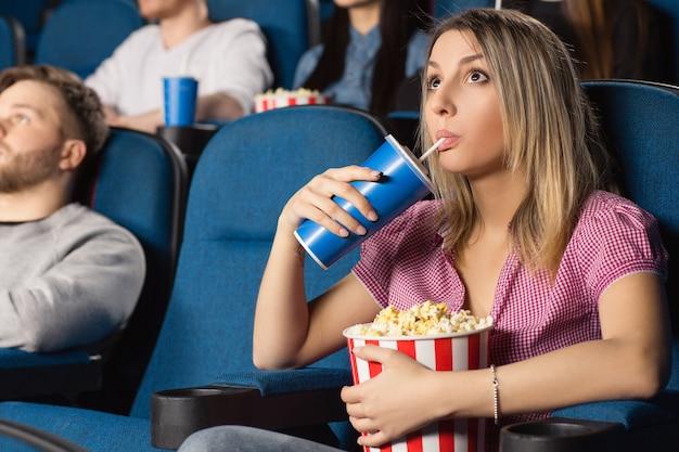 Piękna młoda kobieta pije popkorn i je ogląda filmy w lokalnym kinie