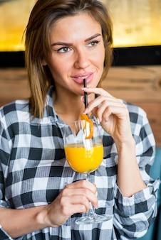 Piękna młoda kobieta pije sok pomarańczowego
