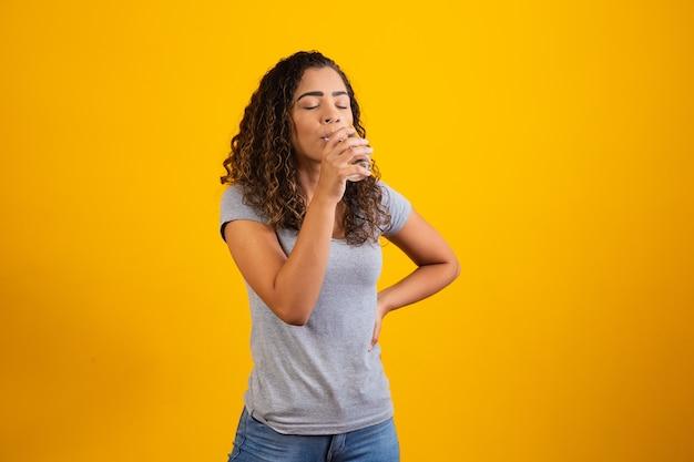 Piękna młoda kobieta pije świeżą szklankę wody