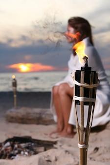 Piękna młoda kobieta pije wino na plaży