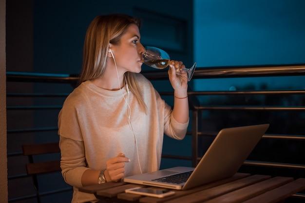 Piękna młoda kobieta pije wino podczas pracy na laptopie w nocy. wysoki obraz iso.