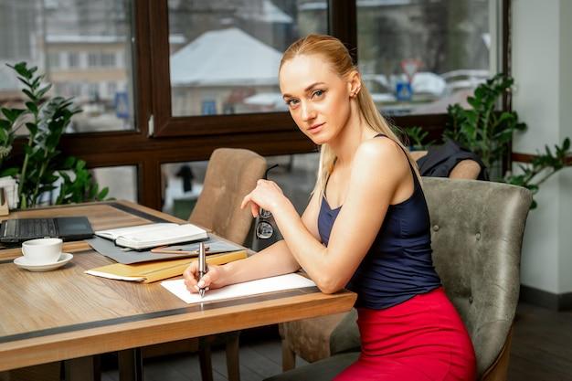 Piękna młoda kobieta pisze dokumenty patrząc na kamery siedząc w kawiarni