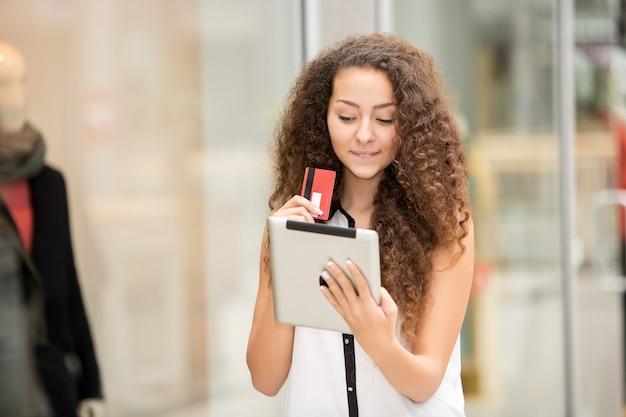 Piękna młoda kobieta płaci kartą kredytową na zakupy