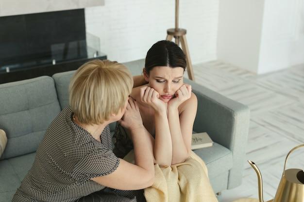 Piękna młoda kobieta płacze na kanapie z rękami na głowie