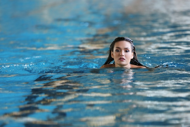 Piękna młoda kobieta, pływanie w basenie