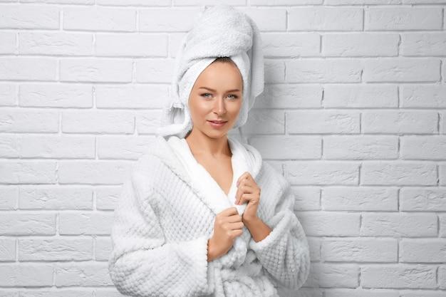 Piękna młoda kobieta po prysznicu na białej powierzchni ściany z cegły