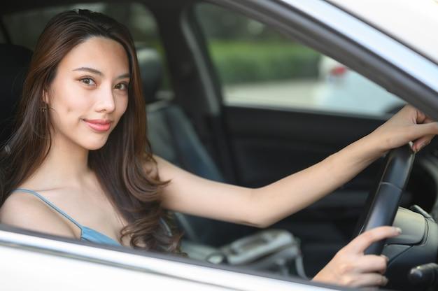 Piękna młoda kobieta podczas prowadzenia samochodu