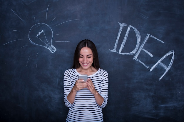 Piękna młoda kobieta podekscytowana pozuje na tle tablicy z obrazem pomysł lampy.