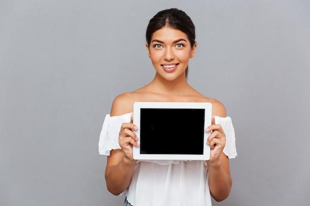 Piękna młoda kobieta pokazuje komputer typu tablet z pustym ekranem na białym tle na szarej ścianie