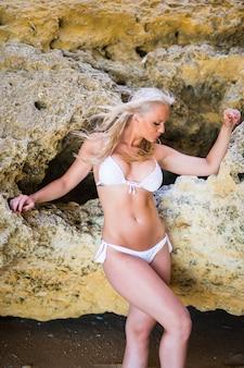 Piękna młoda kobieta pozowanie na plaży ze skałami w białym bikini