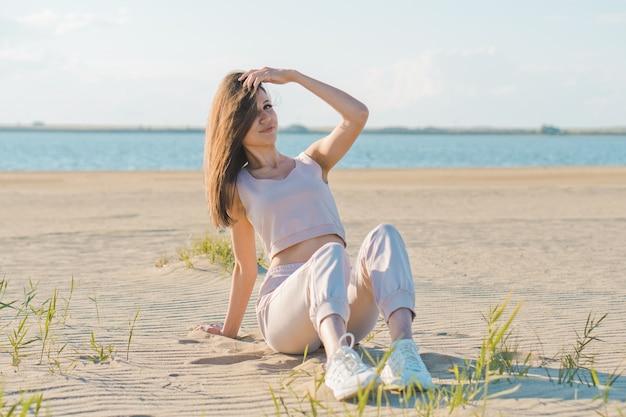 Piękna młoda kobieta, pozowanie na plaży
