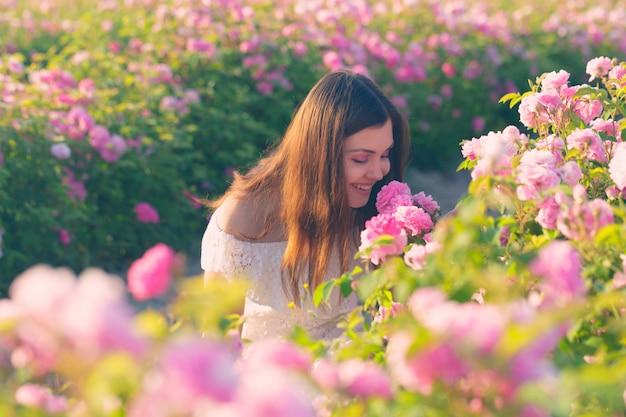 Piękna młoda kobieta pozuje blisko róż w ogródzie,