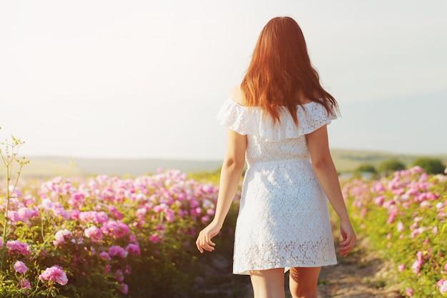 Piękna młoda kobieta pozuje blisko róż w ogródzie.