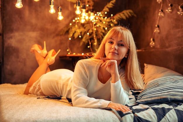 Piękna młoda kobieta pozuje na łóżku