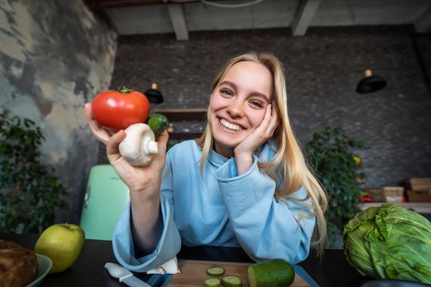 Piękna młoda kobieta pozuje w kuchni