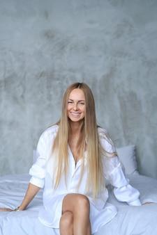 Piękna młoda kobieta pozuje w łóżku