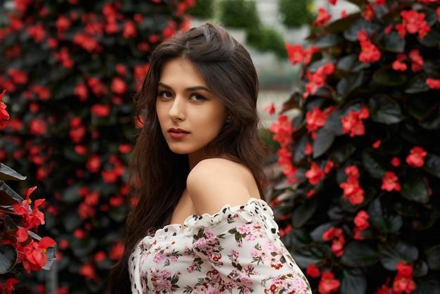 Piękna młoda kobieta pozuje w pobliżu czerwonych kwiatów