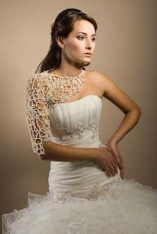 Piękna młoda kobieta pozuje w sukni ślubnej