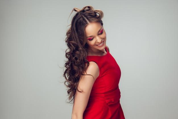 Piękna młoda kobieta pozuje z czerwieni suknią
