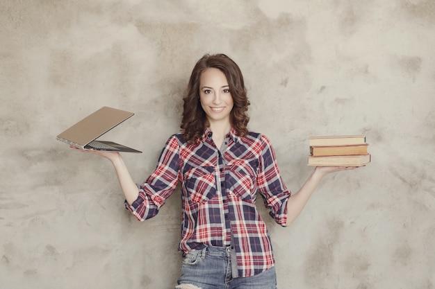 Piękna młoda kobieta pozuje z książkami i laptopem