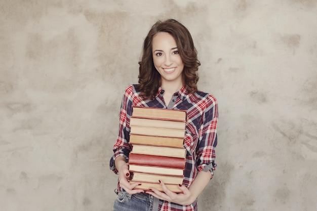 Piękna młoda kobieta pozuje z książkami