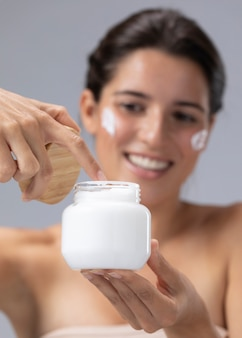 Piękna młoda kobieta pozuje z produktem do pielęgnacji skóry