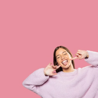 Piękna młoda kobieta pozuje z różową tapetą z tyłu