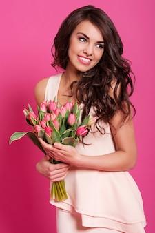 Piękna młoda kobieta pozuje z różowymi tulipanami