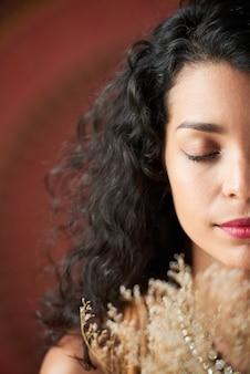 Piękna młoda kobieta pozuje z zamkniętymi oczami dla kreatywnie sesji zdjęciowej