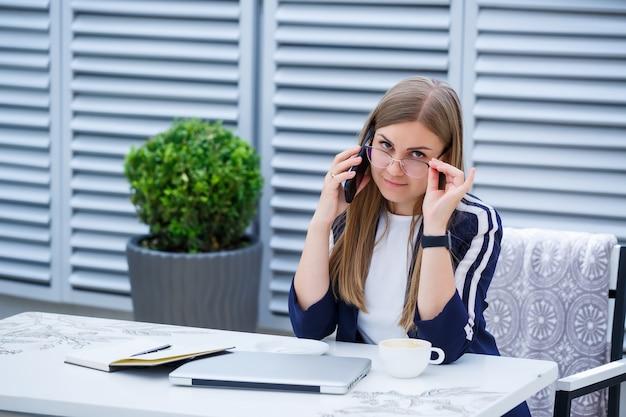 Piękna młoda kobieta pracuje na laptopie i rozmawia przez telefon, uśmiechając się siedząc na świeżym powietrzu w kawiarni. młoda kobieta za pomocą laptopa do pracy. freelancerka pracująca na laptopie w kawiarni na świeżym powietrzu
