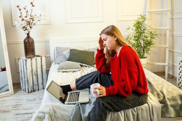 Piękna młoda kobieta pracuje na laptopie, siedząc na łóżku w domu, pije kawę i uśmiecha się. praca w domu podczas kwarantanny. dziewczyna w swetrze i dżinsach w domu na łóżku