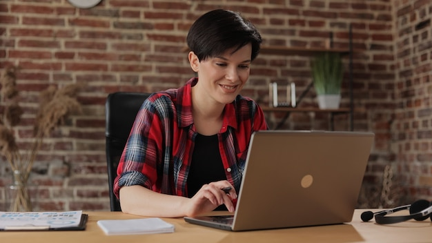 Piękna młoda kobieta pracuje na laptopie