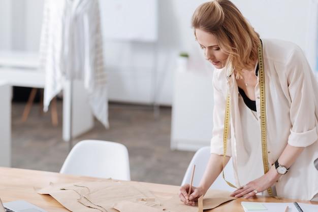 Piękna młoda kobieta pracuje w atelier i pisze ołówkiem na wzorach ubioru, mając na szyi centymetr krawiecki
