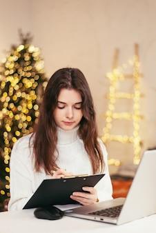 Piękna młoda kobieta pracuje w domu zdalnie za laptopem iz dokumentami na tle choinki. praca w domu