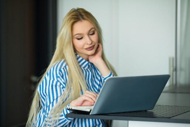 Piękna młoda kobieta pracuje z laptopem w domu, w kuchni