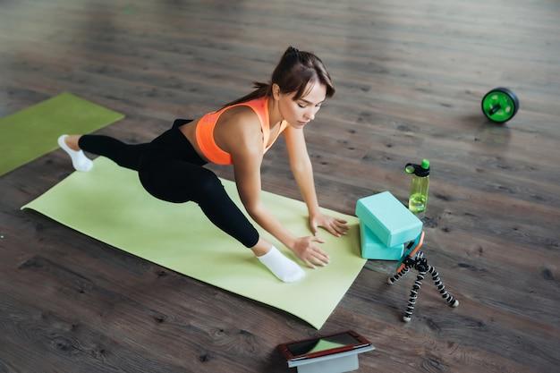 Piękna młoda kobieta praktykuje jogę, jest zaangażowana z nauczycielem online za pomocą tabletu. koncepcja sportu w domu.