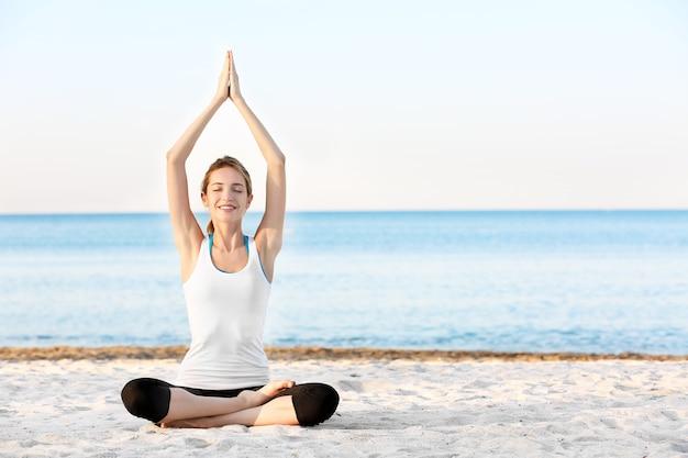 Piękna młoda kobieta praktykuje jogę w nadmorskim kurorcie