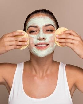 Piękna młoda kobieta próbuje produktów kosmetycznych
