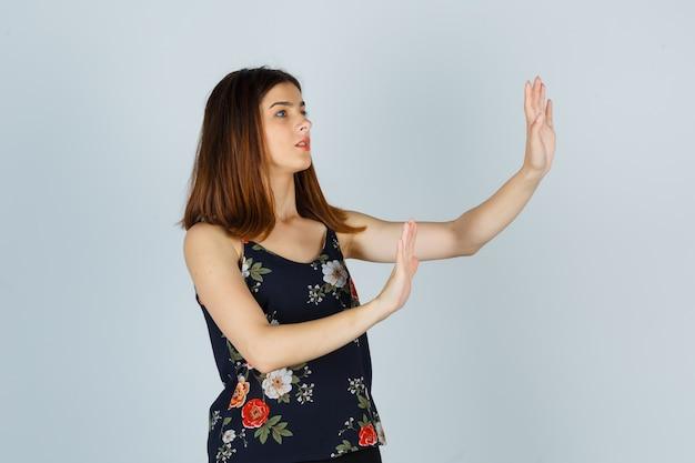 Piękna młoda kobieta próbuje zablokować się rękami w bluzce i wygląda na przestraszoną