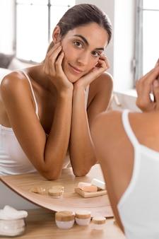 Piękna młoda kobieta przy użyciu produktów i patrząc w lustro