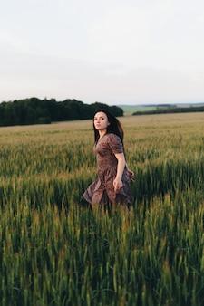 Piękna młoda kobieta przy zmierzchem w polu