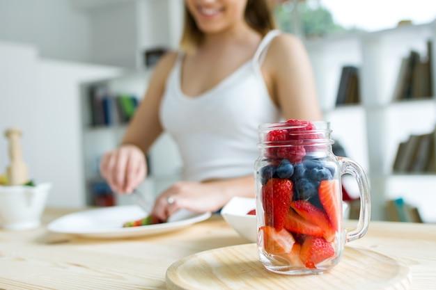 Piękna młoda kobieta przygotowuje śniadanie w domu.