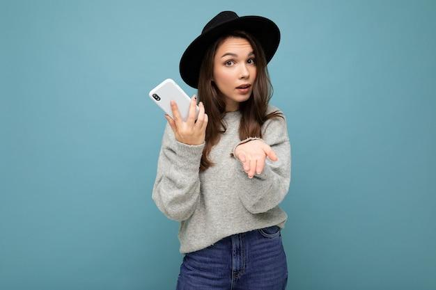 Piękna młoda kobieta pyta niezadowoloną brunetkę pointong ręką w aparacie na sobie czarny kapelusz i szary sweter, trzymając smartfon na białym tle na ścianie.