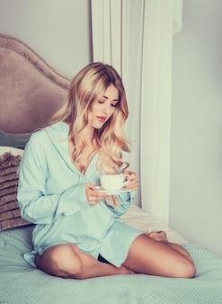 Piękna młoda kobieta rano z filiżanką kawy.