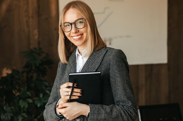 Piękna młoda kobieta rasy kaukaskiej w okularach w garniturze i koszuli stoi w pobliżu biurka, trzymając w rękach notebooka i uśmiechając się z uśmiechem zębatym w biurze.