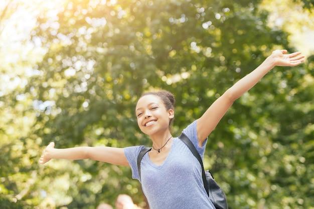 Piękna młoda kobieta rasy mieszanej w parku, poczucie wolności