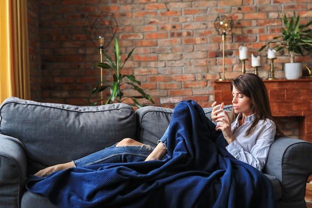 Piękna młoda kobieta relaksując się na kanapie