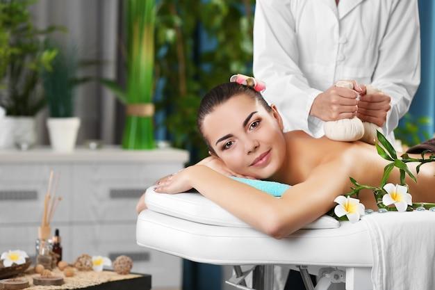 Piękna młoda kobieta relaksująca z masażem dłoni w spa