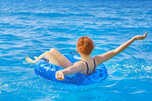 Piękna młoda kobieta relaksuje na nadmuchiwanym pierścionku w wodzie morskiej